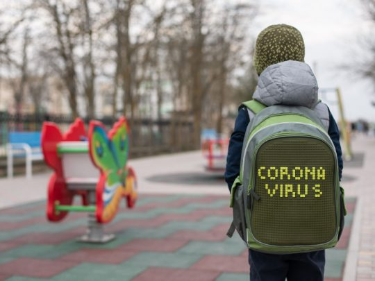 Child with Coronavirus backpack walks toward school