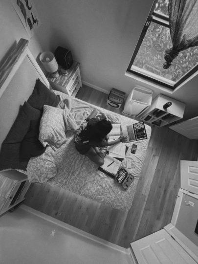 A woman sits on her bed, working on a laptop